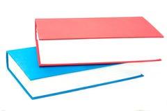 Pila horizontal de dos rojos y de libros azules imagenes de archivo