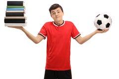 Pila indecisa de la tenencia del adolescente de libros y de fútbol Imágenes de archivo libres de regalías