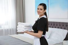 Pila joven de la tenencia de la criada de toallas frescas en hotel imagen de archivo libre de regalías