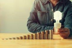 pila llevada tenencia de la luz y del dinero de la mano del hombre de negocios en la tabla en o fotografía de archivo libre de regalías