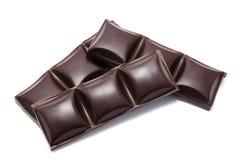 Pila oscura de las barras de chocolate con las migas aisladas Fotos de archivo