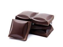 Pila oscura de las barras de chocolate con las migas aisladas imagenes de archivo