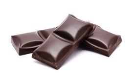 Pila oscura de las barras de chocolate con las migas aisladas Fotos de archivo libres de regalías