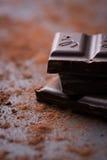 Pila oscura del chocolate con el polvo de cacao en un fondo de piedra Imágenes de archivo libres de regalías