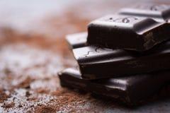 Pila oscura del chocolate con el polvo de cacao en un fondo de piedra Fotos de archivo libres de regalías