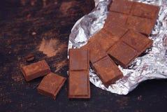 Pila oscura del chocolate con el polvo de cacao en un fondo oscuro con el espacio de la copia, foco selectivo Fotos de archivo