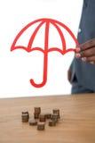 Pila proteggente dell'uomo d'affari di monete con l'ombrello allo scrittorio Immagini Stock
