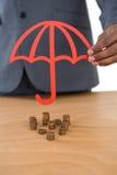 Pila proteggente dell'uomo d'affari di monete con l'ombrello allo scrittorio Immagine Stock