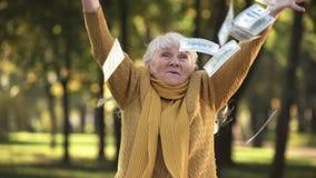 Pila que lanza de la señora mayor mayor feliz de billetes de dólar en parque, retiro previsto fotografía de archivo