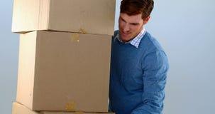 Pila que lleva del hombre de cajas de cartón contra el fondo blanco 4k metrajes