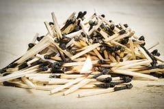 Pila quemada de los partidos con el partido ardiendo en la madera Foto de archivo