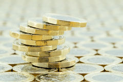 Pila rischioso equilibrata di Britannici le monete da una libbra Fotografie Stock Libere da Diritti