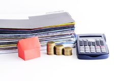 Pila roja del papel y de las monedas de la casa y calculadora y pago de Bill imágenes de archivo libres de regalías