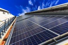 Pila solare sulla cima del tetto contro il cielo soleggiato blu Immagini Stock Libere da Diritti