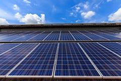 Pila solare sulla cima del tetto contro il cielo soleggiato blu Fotografie Stock