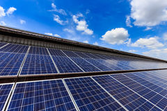 Pila solare sulla cima del tetto contro il cielo soleggiato blu Fotografia Stock
