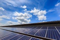 Pila solare sulla cima del tetto contro il cielo soleggiato blu Immagine Stock Libera da Diritti