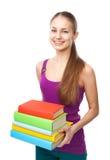 Pila sonriente de la tenencia de la muchacha del estudiante de libros Foto de archivo libre de regalías