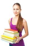 Pila sonriente de la tenencia de la muchacha del estudiante de libros Imágenes de archivo libres de regalías