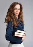 Pila sonriente de la tenencia de la mujer de negocios de libros Foto de archivo