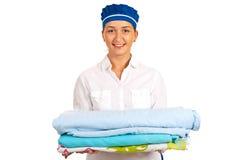 Pila sorridente della tenuta della domestica di lenzuolo immagini stock libere da diritti
