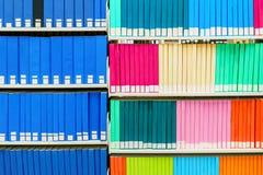 Pila variopinta di libri di ricerca in una biblioteca universitaria, con le spine dorsali in bianco del libro Utile come fondo fotografia stock