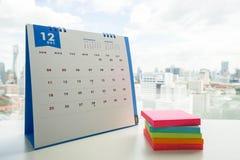 Pila variopinta di Post-it con il calendario di dicembre Fotografia Stock Libera da Diritti