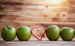 Pila verde de la manzana del primer en fila y corazón rojo fotos de archivo libres de regalías