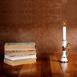 Pila vieja de libros con la palmatoria y la vela ardiente Imágenes de archivo libres de regalías