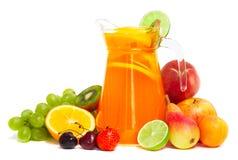 Pila y jugo de la fruta en la jarra aislada en blanco imagenes de archivo