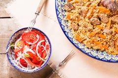 Pilaf και achichuk σαλάτα στο χειροποίητο πιάτο στο ξύλινο υπόβαθρο Στοκ Εικόνα