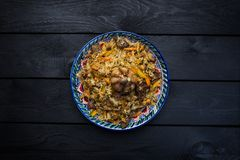 Pilaf στο πιάτο με την ασιατική διακόσμηση σε ένα ξύλινο υπόβαθρο Κεντρικός-ασιατική κουζίνα - Plov Τοπ όψη Στοκ φωτογραφία με δικαίωμα ελεύθερης χρήσης