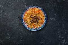 Pilaf στο πιάτο με την ασιατική διακόσμηση σε ένα σκοτεινό υπόβαθρο Κεντρικός-ασιατική κουζίνα - Plov Τοπ όψη Στοκ Εικόνα