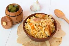 Pilaf с мясом от шара на деревянной доске и белой предпосылке, соленьях бочонка, чесноке, деревянной ложке Стоковая Фотография RF