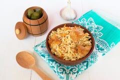 Pilaf с мясом от шара на деревянной доске и белой предпосылке, соленьях бочонка, чесноке, деревянной ложке Стоковая Фотография