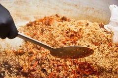 Азиатское традиционное блюдо - pilaf Варить pilaf в котле Рис с мясом и овощами стоковое фото rf