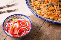 Pilaf and achichuk salad in handmade plate on wooden background Royalty Free Stock Image