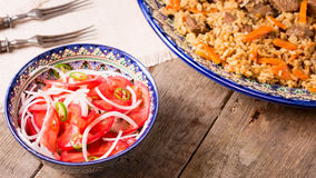 Pilaf and achichuk salad in handmade plate on wooden background Stock Photography