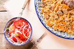 Pilaf and achichuk salad in handmade plate on wooden background Stock Image