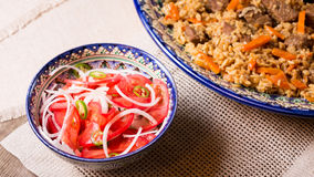 Pilaf and achichuk salad in handmade plate on wooden background Royalty Free Stock Photos