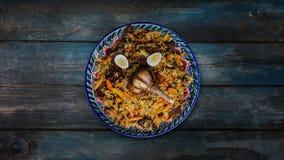 Pilaf auf Platte mit orientalischer Verzierung Zentral-asiatische Küche - Plov Dreht sich auf hölzernen Hintergrund Beschneidungs stock footage