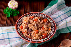 Pilaf on the brown plate on a wooden table, background. Rustic style. Stock Images