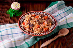 Pilaf on the brown plate on a wooden table, background. Rustic style. Royalty Free Stock Photo