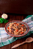 Pilaf on the brown plate on a wooden table, background. Rustic style. Stock Image