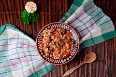 Pilaf on the brown plate on a wooden table, background. Rustic style.  Top view. Stock Photos