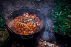 Pilaf in the cauldron on the fire stock images