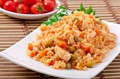 Pilaf con el pollo, la zanahoria y los guisantes verdes Fotografía de archivo