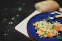 Pilaf del arroz con los albaricoques, hojas de menta, en una placa azul marino en fondo del negro del tablero de madera Fotografía de archivo libre de regalías