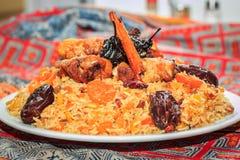 Pilaf dulce con el pollo, las pasas, los albaricoques secados, la pera condimentada y los palillos de canela Imagen de archivo libre de regalías