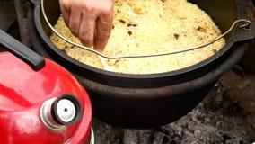 Pilaf in einem großen Kessel draußen kochen stock video
